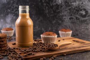 café na garrafa com grãos de café e muffins foto