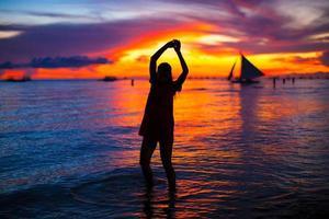 jovem mulher bonita na praia tropical ao pôr do sol foto