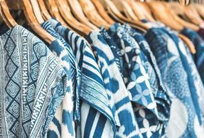 close-up de camisas azuis em cabides de madeira