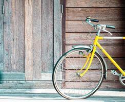 bicicleta amarela em uma parede de madeira foto