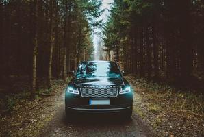 mallorca, espanha, 2020 - land rover range rover suv em uma estrada de terra entre árvores verdes foto