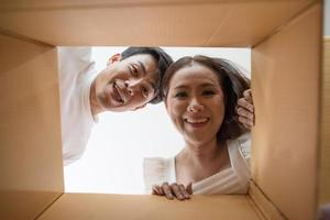 casal feliz abrindo uma caixa e olhando dentro