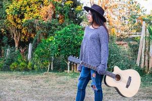 mulher caminhando com um violão foto