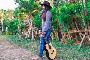 mulher segurando um violão enquanto caminha foto