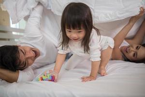 criança feliz com pais brincando na cama foto