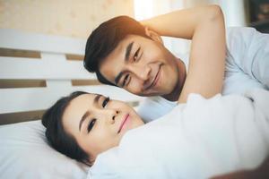 casal feliz deitado na cama foto