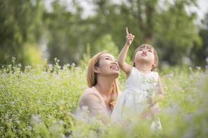 mãe e filha brincando juntas em um campo de flores silvestres