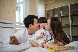 criança feliz com pais brincando em casa foto