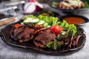 porco frito coberto com pimenta e vegetais foto