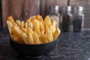 batatas fritas em uma tigela preta foto