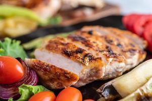 bife de frango com salada de legumes em um prato preto foto