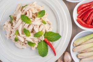salada de frango em um prato branco com folhas de hortelã foto