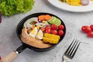 salada de legumes com pão e ovos cozidos foto