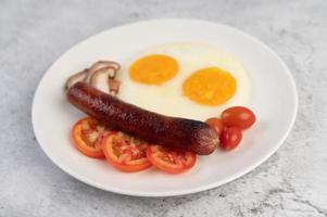 prato de café da manhã com ovos fritos, tomate, linguiça chinesa e cogumelos foto