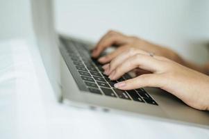 mãos de mulher digitando no laptop foto