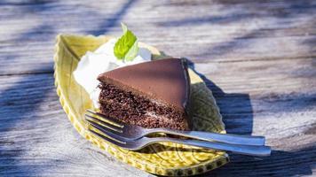 Bolo de chocolate fudge servir com creme na mesa de madeira vintage.