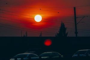 2018 janeiro Banguecoque, Tailândia. as pessoas viajam em carros particulares em um grande problema de congestionamento de tráfego de cidade grande. sol vermelho pôr do sol na rua da cidade. cidade e engarrafamento à noite com lindo pôr do sol laranja