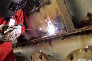 soldador na suíte vermelha soldando o invólucro de aço