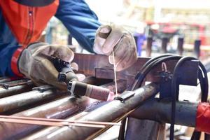o soldador está soldando a placa ao tubo