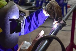 soldador trabalhando com equipamento de proteção