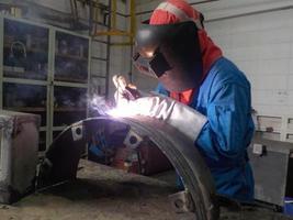 soldador de uniforme azul soldando a peça de trabalho