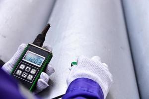inspetor medindo a espessura do tubo