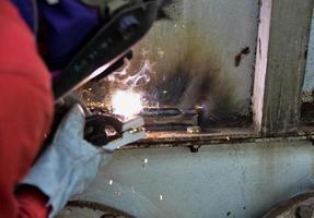 soldador na suíte vermelha soldando o revestimento de aço da fábrica