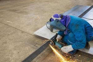 trabalhador de uniforme azul cortando chapas de metal