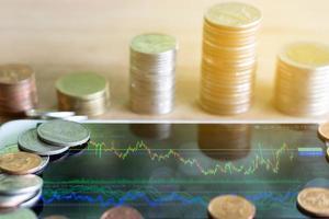 gráfico forex de exibição de smartphone com pilha de moedas.