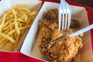 comendo frango frito com batatas fritas foto