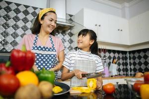 mãe e filha se ajudam na cozinha de casa foto