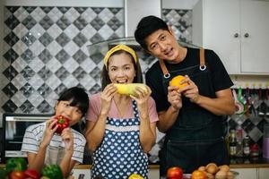família feliz cortando vegetais juntos na cozinha