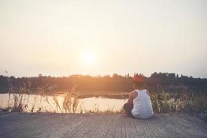 menino triste sentado perto da água