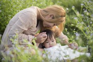 mãe e filha brincando juntas em um prado