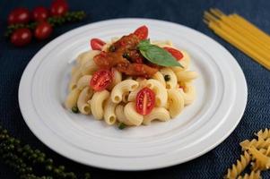 macarrão frito com tomate, pimenta, sementes de pimenta e manjericão foto