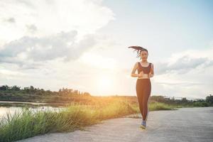 uma jovem e feliz corredora correndo ao ar livre foto