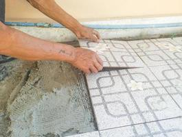 a mão do trabalhador está colocando adesivo de azulejos foto