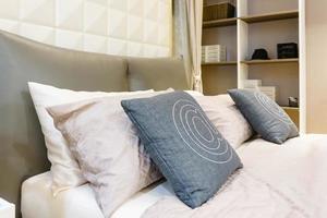 cama arrumada com travesseiros brancos limpos e lençóis no salão de beleza, close-up.
