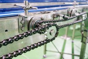 o eixo de transmissão da engrenagem e da corrente na corrente transportadora e na correia transportadora está na linha de produção.
