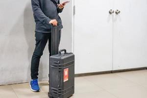 jovem asiático usando smartphones com sua bagagem para verificação de voos em aeroportos, conceito de viagens ao exterior