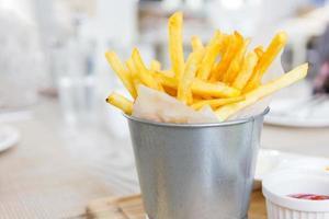 Batatas fritas, embrulhadas em papel em um balde de aço inoxidável sobre uma mesa de madeira, foco seletivo foto