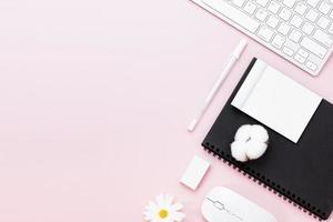 mesa de mesa de escritório mínima com teclado de computador, mouse, caneta branca, flores de algodão, borracha em uma mesa rosa pastel com espaço de cópia para inserir seu texto, composição do local de trabalho cor-de-rosa, disposição plana, vista superior