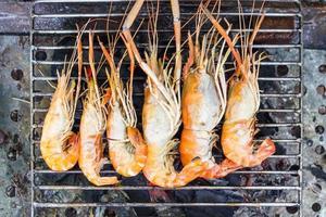 camarão do rio ou camarão do rio churrasco de frutos do mar grelhados no fogão a carvão. close-up com comida cozida, frutos do mar tailandês foto