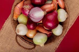 vista superior de diferentes tipos de cebola em uma cesta em pano de saco sobre fundo vermelho foto