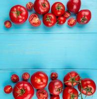 vista superior de tomates cortados e inteiros em fundo azul com espaço de cópia