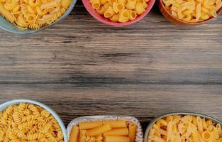 vista superior de diferentes macaronis como rotini ziti e outros em fundo de madeira com espaço de cópia foto