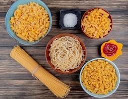 macaronis como espaguete rotini vermicelli e outros com sal e ketchup em fundo de madeira foto