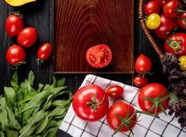vista de cima de vegetais como tomate manjericão na cesta e tomate cortado na bandeja com folhas verdes de hortelã em fundo de madeira foto