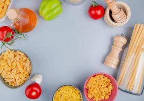 vista superior de diferentes tipos de macarrão como tagliatelle ziti pipe-rigate bucatini com tomate sal alho pimenta preta manteiga em fundo azul com espaço de cópia foto