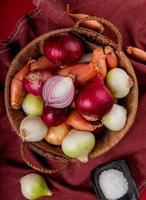 vista superior de cebolas diferentes na cesta com sal no pano de bordo e fundo vermelho foto